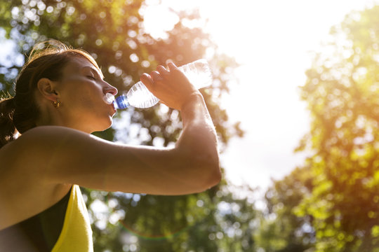 Young beautiful brunette drinking water from a bottle after running workout