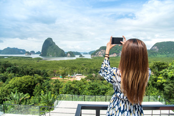 Women tourist he is shooting a beautiful scenic view by mobile phone at Phang Nga Bay, Samet Nang She Viewpoint,Thailand