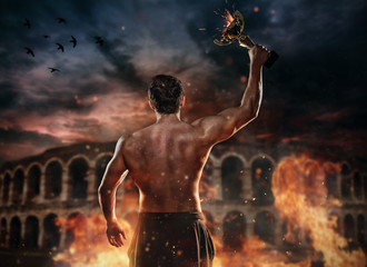 Back view of muscular man holding burning trophy cup, antique colosseum on background.
