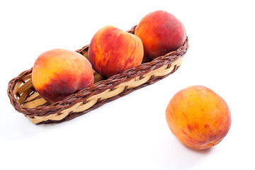 Single ripe peach fruit and several in basket isolated on white background.