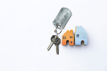 Miniature house with house key on white background, real estate and property business concept