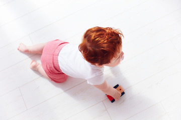top view of redhead baby boy rolling a toy car on the floor