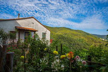 Isolated house in the countryside with garden and flowers under a blue sky with little clouds