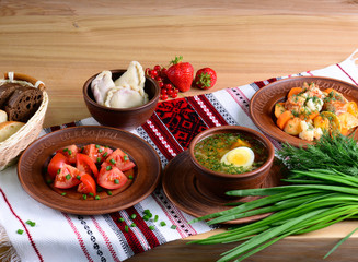 Traditional national food of Ukraine: vegetable soup with boiled egg, salad with tomatoes in sunflower oil, vareniki with berries, vegetable stew on a tablecloth with ornament. Original feed.