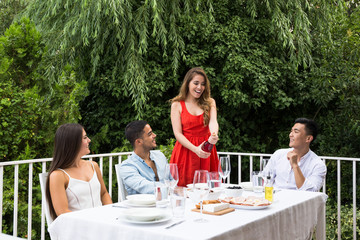Cheerful girl opening bottle of pink wine while having lunch with friends in garden.