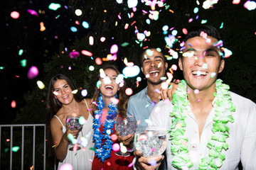 Group of laughing friends posing with cocktails in darkness with flying confetti in air.