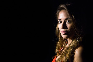 Portrait of young pretty girl looking at camera while posing sensually in spotlight in darkness.