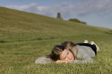 Ein junges Mädchen liegt entspannt auf einem Rasen