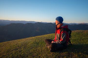 Adventurer admiring panorama of mountains during sunset