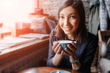 A beautiful asian woman drinking hot coffee or tea from vintage cup in modern loft cafe