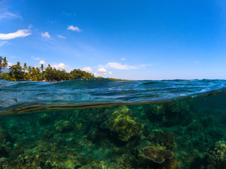 Split photo with tropical island and coral reef. Clear blue sky and underwater view.