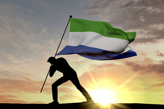 Sierra Leone flag being pushed into the ground by a male silhouette. 3D Rendering