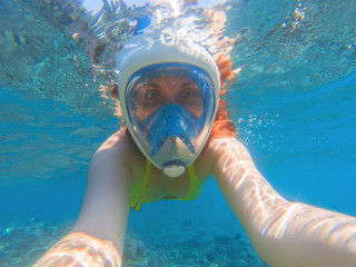 Snorkeling in full face mask. Summer activity. Beautiful girl in shallow seawater.