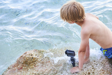 Child boy shooting movie with action outdoor waterproof camera in the sea