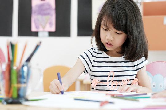Girl drawing color pencils in kindergarten classroom, preschool and kid education concept
