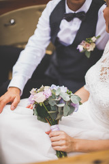 Bride and groom holding bridal bouquet