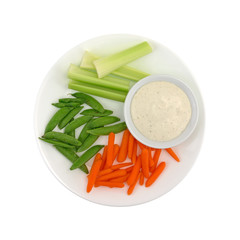 Veggies on a plate with ranch dressing to the side isolated on a white background.