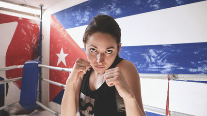 Young female doing shadow boxing exercise in a boxing ring. .