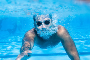 Underwater enjoyment. Young man swimming underwater and diving in the swimming pool.