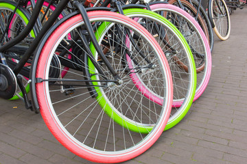 Three Dutch bikes with colorful fluorescent tires in pink and green