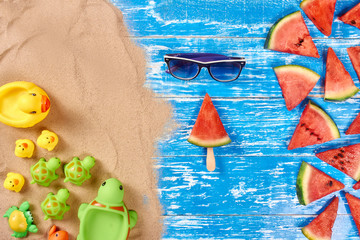 Summer background with watermelon slices, sunglasses, sand, Yellow rubber ducks, Green turtles