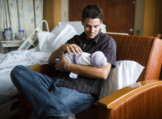 Smiling man with brown hair sitting in armchair, holding newborn baby.