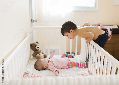 Young boy with brown hair leaning over a baby wearing pink onesie lying on her  back in a crib. a44a127d262c