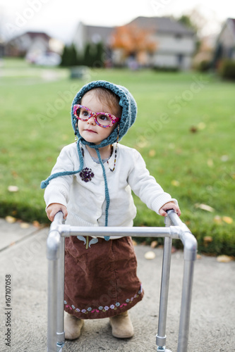 a toddler girl wearing a halloween costume of an elderly woman in a suburban neighborhood