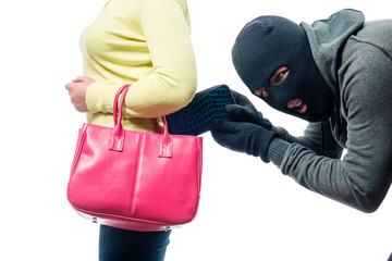 A thief pickpocket steals a purse from a women's bag in a balaclava