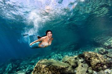 Beautiful Mermaid swimming underwater in the deep blue sea