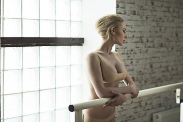 Slender blonde girl ballerina in bright dancing hall. Woman with big breast and in beige underwear standing near handrail.