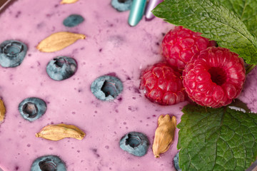 Close-up of a glass of fresh and cold pink smoothie as a background. A nutritious cocktail full of berries and mint.