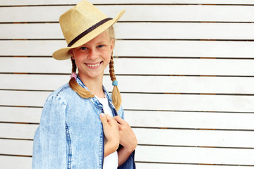 Happy child against white wooden wall. Style concept.