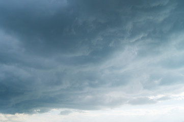 Grey dark fkuffy clouds on the blue sky at sunset or sunrise. Stormy weather.