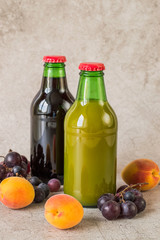 Two glass bottles with natural fruit juice, fresh apricots and grapes on a gray background. The concept of a healthy diet.