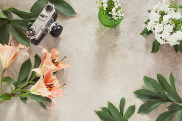 Vintage desk table with camera and flower. Top view with copy space. Female creative concept.