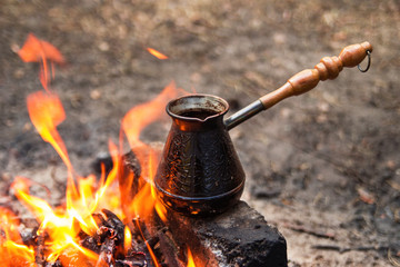 Metal cezve with hot flavored coffee on a bonfire closeup.