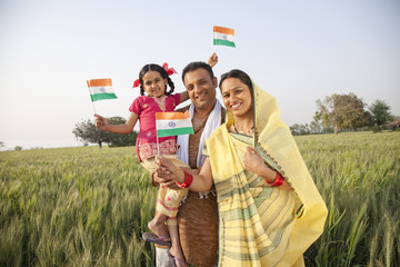 Portrait of a rural family holding an Indian flag