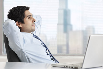 Side view of thoughtful businessman relaxing at his desk