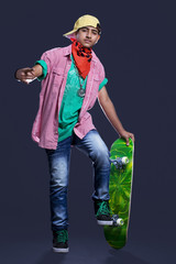 Full length of teenage boy posing with skateboard against black background
