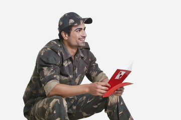Smiling young soldier holding greeting card and looking away