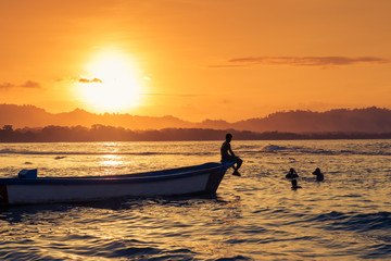 People swimming at the beach in Puerto Viejo de Talamanca, Costa Rica, at sunset