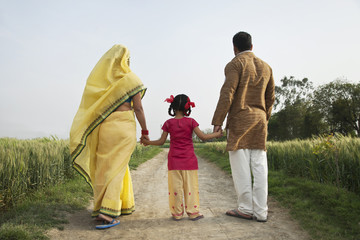 Back view of family walking together on a rural road
