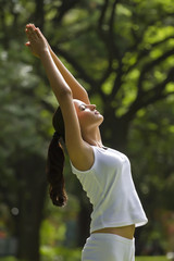 Young woman doing yoga with hands outstretched