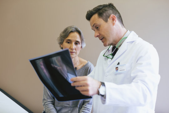 Doctor explaining x-ray image to patient in clinic