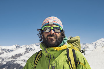 Smiling hiker in sunglasses standing on mountain against clear blue sky during winter