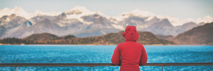 Alaska cruise travel tourist woman banner watching nature landscape from boat. Panoramic background crop of inside passage, Glacier Bay, USA.