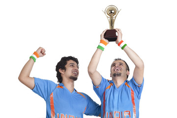 Happy young male friends in jerseys cheering up with winning trophy over white background