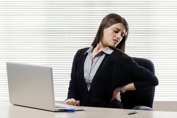 Businesswoman getting a backache in office