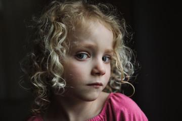 Portrait of girl sitting against black background